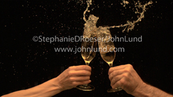 A champagne toast splashing out of the champagne flutes (glasses) in a dramatic and slow motin video showing celebration, success and romance.