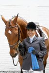 Picture of a woman standing next to her horse and proudly showing the blue ribbon she won in the competition. The woman is wearing her riding gear and holding the reins of the horse.