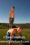 A young boy is standing on his dads back and his father is on all fours on the green grass. The father and boy have on bathing suits. Sky is dark blue with no clouds.