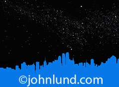 A blue city skyline appears against a black star filled night sky in a simple graphic image in a visual metaphor for urban centers, large cities, and the possibilities that exist therein.
