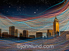 Wireless communications technology, particularly in an Urban environment, as well as networking, connections and cloud computing are all represented in ths stock photo of colorful lights streaking in an around the tall buildings of an unidentified metropo