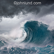 A classic ocean wave curls over beneath stomry skies in a stock photo about the ocean, nature and philosophy.