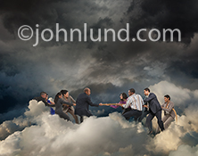 In the cloud, two groups of business people have an intense competition as the engage in a tug of war contest to illustrate the concept of challenges in cloud computing.