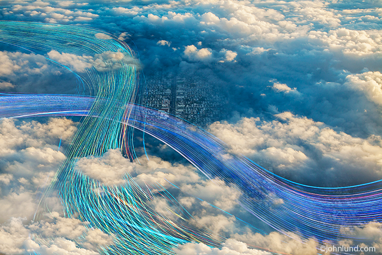 "Streaks of ""business blue"" lights wind their way through clouds and over a city in this photo of cloud computing made visible."