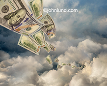 A stream of hundred dollar bills flows through the clouds in a stock photo about cash flow and cloud computing.