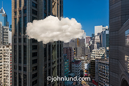 Cloud computing in the city is simply and effectively portrayed in this stock photo of a single cloud nestled among the high rise buildings of a major metropolis.