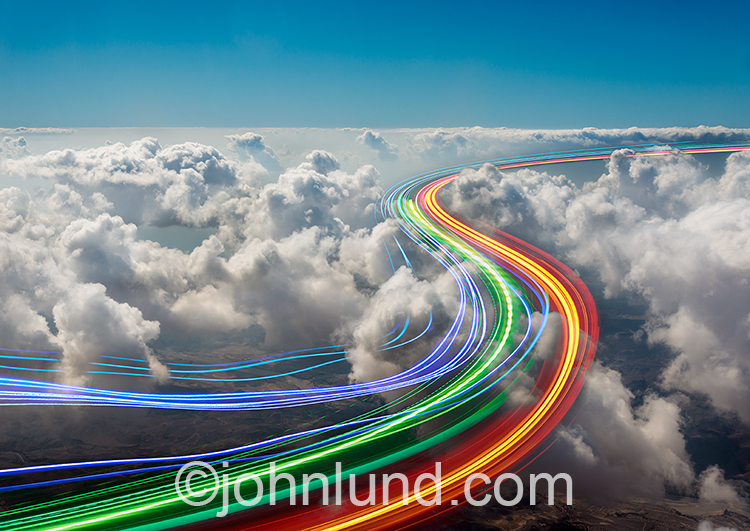 Cloud computing, fast streaming data, and connections are colorfulling illustrated in this stock photo of vibrant colored lines streaking through a layer of clouds.