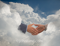 A handshake takes place in a cloudscape in this photo illustrating the concepts of cloud computing, Internet connections, and teamwork.