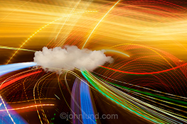Cloud computing connections are dramatically illustrated in this stock photo featuring a single cloud amid a tangle of light trails that stream from and through the cloud showing networking, connections, streaming data and more.