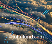 What could be a better image about cloud computing, networks and communications technology than an aerial shot looking down on clouds that are being pierced by streaking colored lights of streaming data.