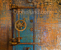 Technology security is illustrated in this photo of complex computer circuitry overlayed on top of a bank vault door.