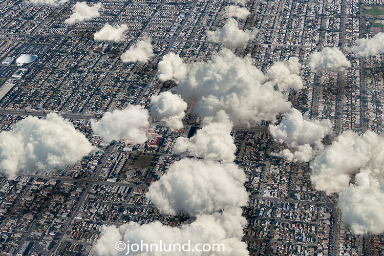 A central cloud expands out in mutliple directions in this cloud computing photo that includes an aerial view of Los Angeles and is a metaphor for everything from computer servers to distributed computing to networking and connections via cloud computing.