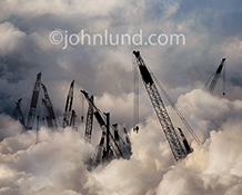 Cloud construction and infrastructure development are the primary concepts in this stock photo that shows a series of construction cranes positioned in a cloud bank representing cloud computing.