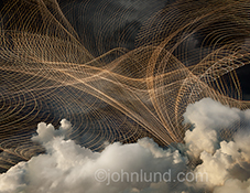Cloud computing, networks, and the Internet are all symbolized in this stock photo of an intricate network of light trails flowing through storm clouds.