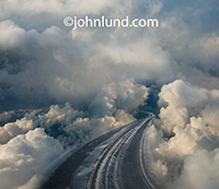 A highway curves up into the clouds in a metaphor for cloud computing and online storage, archiving and networking.