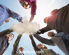 Teamwork in the cloud, online connections, and business links are all concepts illustrated with this image of a group of business people joining hands in a small centrally located cloud.