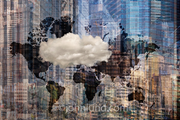 Cloud computing with global reach and connections is illustrated in this stock photo of a single cloud against an abstract collage background of high rise buildings and a map of the world continents.