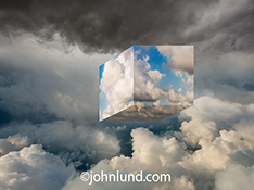 A cube of clouds is floating in a cloud bank in an image about the infrastructure of the cloud, and the cloud within the cloud; a stock photo useful for bringing attention to all manner of cloud computing issues.
