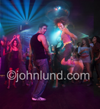 A couple is dancing in the forefront of a nightclub or rage complete with colored lights and disco ball in a high energy scene.
