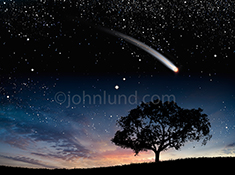 A comet arcs through the night sky at twilight with a trail of burning debris in a stock photo about mystery, ideas, and outerspace.