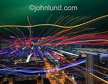 Vivid streaks of light speed out from and over a sprawling metropolis at night in a vivid display of communications technology, streaming data and connections.