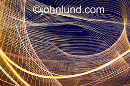 A complex light pattern of light trails forms a web in a stock photo about communications technology, the Internet, and networking.