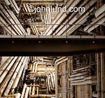 A catwalk crosses through an incredibly complex arrangement of industrial pipes in a metaphor for complexity and potential problems.