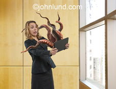 A horrified woman holds a computer tablet from which tentacles are emerging and grasping for her in a picture about computer problems, malware and spam.
