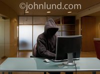 Computer hacking is the concept behind this photo of a mysterious figure, face unseen, wearing a dark hoodie and using a computer in a corporate office setting.