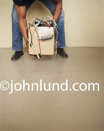Picture of a man lifting a box of computer parts and cords. Only the mans arms and legs are visible. The man lifting the box of cords, wires, and computer parts is not lifting the box properly. He should be bending his knees and lifting with his legs.