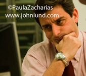 A concerned businessman is looking worriedly at his computer screen display. His hand is on his chin and his brow is wrinkled. Short dark hair.  Worried Businessmen photos.