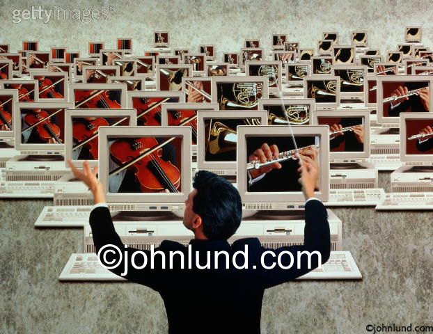 Stock photo of a conductor leading an orchestra of computers showing teamwork, connection, leadership and networking.
