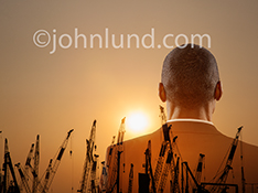 A businessman gazes out at the sunset over a line of construction cranes in an image about construction, business growth, and the future.