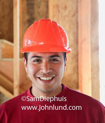 Happy smiling portrait of a male hispanic construction worker in an orange hard hat and smiling right at the camera. He has a little chin stubble or slight growth of beard and a friendly happy smile lights up his face.