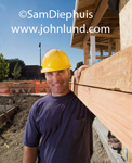 Picture of hard working construction worker carrying a heavy load. The average looking man has a couple of heavy wooden beams over his shoulder and is wearing a yellow hard hat.  Advertsing pictures of average looking men.