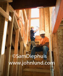 Picture of a construction worker sitting on the stairs in a stair well working on his laptop in a bulding under construction. Behind him is a carpenter driving or hammering a nail into a window sill. Bare framing surrounds the two construction workers.