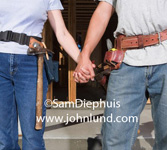 Picture of working couple holding hands. They are carpenters or construciton workers judging by the tool belts hung on their waists. Torso only no heads in shot.  Woman worker and male worker holding hands at the job site. Pics for ads.
