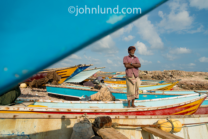 A fisherman on the island of Socotra stands on his boat in contemplation.
