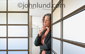 A woman executive contemplates an important business decision as she stands between two walls of glass panels in an upscale corporate business  office environment.