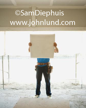 A male workman with a toolbelt on his waist is holding up a set of blueprints which hide his face from view.  Bright white sunlight behind him. Photo of a construction worker with toolbelt looking at a set of building plans.
