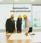 Picture of contractors. Three people in hard hats in a high rise office are examining blue prints on a conference table. Two men and a woman architects looking at blue prints. Pictures of contractors working.