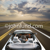 Beautiful picture of a couple in a convertible sports car driving towards a sunset/sunrise on a long straight road.