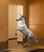 A unicorn rears up in a corporate lobby in an image about mythical, magical and