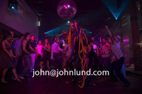 Man wearing a costume dancing at a disco club in Rio. Strobe lights, multi-colored lights, spot lights, black lights, nightclub atmosphere.