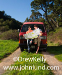 A couple on a road trip is leaning against the front of thier camper van and reading a road map.  She is wearing torn jeans and he has on shorts.  Couple is holding map together. Trees and green grass everywhere.