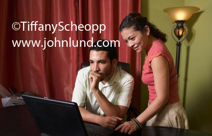 Photo of a hispanic couple looking at their laptop.  He is seated at the desk and she is standing next to him.