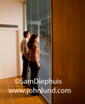 A couple, a man and a woman, are standing vey close to a window and facing the window looking out. Both the man and the woman have their hands in their pockets. Standing in a hallway looking out a window.