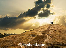 Romance and love are the primary concepts in this image of a couple holding hands and silhouetted as they crest a hill against a dramatic setting sun breaking out of a low cloud bank.