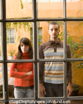 Picture of an unhappy couple standing next to each other facing the camera viewed through a window. The couple might be fighting or maybe they are just pissed off at each other. The silent treatment.