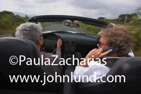 Senior couple driving a small convertible sports car with the top down. The woman is driving and has short gray hair.  Her passenger, a senior man, is on his cell phone. The top is down on the car. Seniors driving pic.